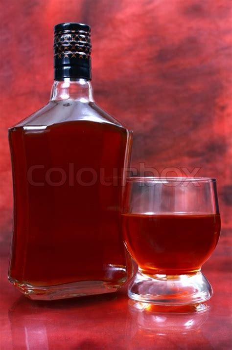 Alcohol drink is in a bottle and glass on red background